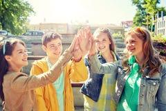 Lyckliga studenter eller vänner som gör höjdpunkt fem royaltyfri fotografi