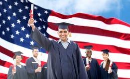 Lyckliga studenter i akademikermössor med diplom Arkivbilder