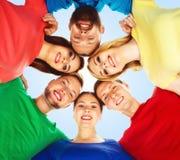Lyckliga studenter i färgrika kläder som tillsammans står Utbildning Arkivfoton