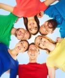 Lyckliga studenter i färgrika kläder som tillsammans står Utbildning Royaltyfria Bilder