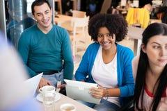 Lyckliga studenter i kafé arkivbild