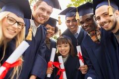 Lyckliga studenter i mortelbräden med diplom Arkivbilder