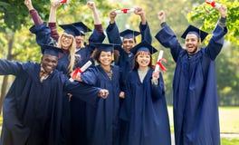 Lyckliga studenter i mortelbräden med diplom Arkivfoton