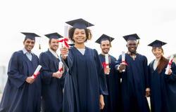 Lyckliga studenter i mortelbräden med diplom Fotografering för Bildbyråer