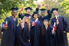 Lyckliga studenter i mortelbräden med diplom Royaltyfria Bilder