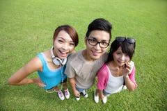 Lyckliga studenter i universitetsområde Arkivfoto