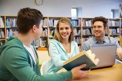Lyckliga studenter med bärbara datorn och boken på arkivet royaltyfri foto