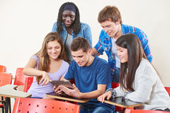 Lyckliga studenter med en minnestavla royaltyfri bild