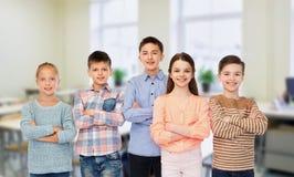 Lyckliga studenter på skolan över klassrumbakgrund royaltyfria bilder
