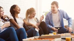 Lyckliga studenter som äter pizza och hemma skrattar arkivbilder