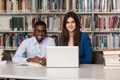 Lyckliga studenter som arbetar med bärbara datorn i arkiv Royaltyfri Foto