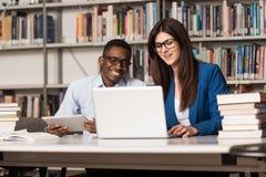 Lyckliga studenter som arbetar med bärbara datorn i arkiv Royaltyfria Foton