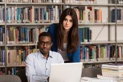 Lyckliga studenter som arbetar med bärbara datorn i arkiv Arkivbilder