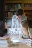 Lyckliga studenter som arbetar samman med futuristisk manöverenhet Arkivfoto
