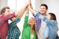 Lyckliga studenter som ger höjdpunkt fem på skolan Arkivbild