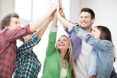 Lyckliga studenter som ger höjdpunkt fem på skolan royaltyfri bild