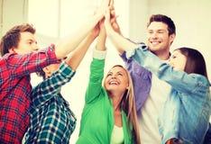 Lyckliga studenter som ger höjdpunkt fem på skolan royaltyfria foton