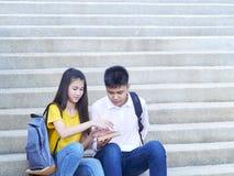 Lyckliga studenter som ?r utomhus- med b?cker royaltyfri bild