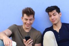 Lyckliga studenter som ser smartphonen utanför på universitetsområde på universitetet royaltyfri fotografi