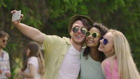 Lyckliga studenter som tar selfie och att tycka om sommarferier, att krama och att dansa arkivfilmer