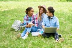 Lyckliga studenter som tycker om avbrottet på gräsmatta royaltyfri fotografi