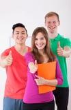 Lyckliga studenter som visar tummar, up tecknet Arkivfoton