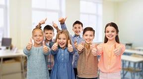 Lyckliga studenter som visar upp tummar på skolan royaltyfri bild