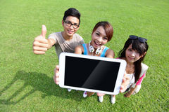 Lyckliga studenter visar den digitala minnestavlan Arkivfoto