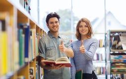 Lyckliga studentpar med böcker i arkiv Royaltyfri Bild