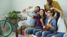 Lyckliga studentvänner som tar selfie på smartphonekamera och poserar, medan ha det hem- partiet i delat boende stock video