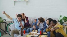 Lyckliga studentvänner som tar selfie på smartphonen och poserar, medan ha partiet med öl och pizza, i delat arkivfilmer
