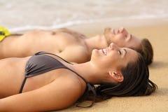 Lyckliga sunbathers som solbadar på sanden av stranden royaltyfri foto