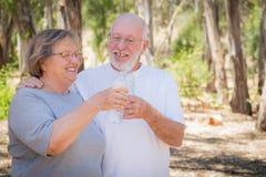 Lyckliga sunda höga par med vattenflaskor Arkivfoton