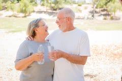 Lyckliga sunda höga par som utomhus skrattar med vattenflaskor Royaltyfria Bilder