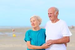 Lyckliga sunda pensionerade fläderpar som tycker om semester på stranden Arkivbilder