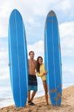 Lyckliga surfare som surfar par som poserar med surfingbrädan Fotografering för Bildbyråer