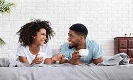 Lyckliga svarta par som dricker kaffe i säng royaltyfri bild