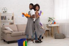 Lyckliga svarta par som rymmer tvättmedel under att göra ren hemma royaltyfria bilder