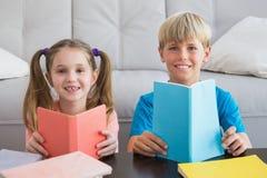 Lyckliga syskonläseböcker på golv Royaltyfri Foto