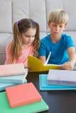 Lyckliga syskonläseböcker på golv Fotografering för Bildbyråer
