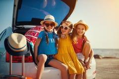 Lyckliga systrar f?r barnflickav?nner p? bilritten till sommarturen arkivfoton
