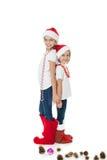 Lyckliga systrar i santas hattar och gåvasockor Royaltyfri Foto