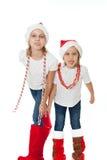 Lyckliga systrar i santas hattar som visar av, spontar att reta Fotografering för Bildbyråer