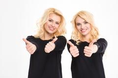 Lyckliga systrar kopplar samman upp visningtummar Arkivbilder