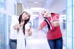 Lyckliga systrar på framgång i kontoret Arkivfoton