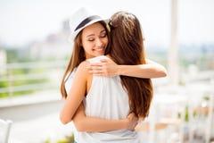Lyckliga systrar som kramar sig: förälskelse och omsorg, förtroende och toget Royaltyfria Foton