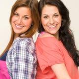 Lyckliga systrar som ler och ser kameran Arkivfoto