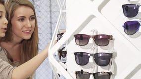 Lyckliga systrar som shoppar för eyewear på optometrikerlagret stock video