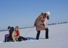 lyckliga systrar som sledding Arkivfoton