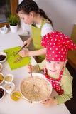 Lyckliga systrar som tillsammans lagar mat Arkivfoto